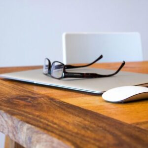 Laptop and glasses sitting on a desk.